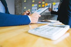 deux cadres commerciaux analysant le papier de données sur le lieu de travail image libre de droits