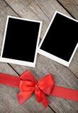 Deux cadres de photo au-dessus de fond en bois avec l'arc rouge photo libre de droits