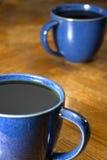 Deux cafés noirs dans des tasses bleues Photographie stock