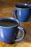 Deux cafés noirs dans des tasses bleues Photo stock