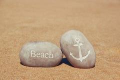 Deux cailloux en pierre avec la plage et l'ancre de mot signent plus de la plage sablonneuse photos stock