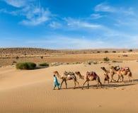 Deux cameleers avec des chameaux en dunes de deser de Thar Photographie stock libre de droits