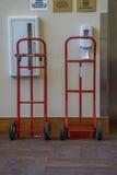 Deux camions de main rouges attendant pour être utile Photographie stock libre de droits