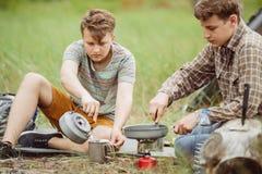 Deux campeurs semblables faisant le thé et préparant la nourriture Images libres de droits