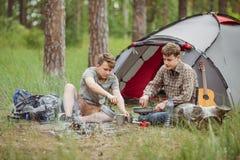 Deux campeurs semblables faisant le thé et préparant la nourriture par une tente Images libres de droits