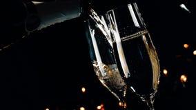 Deux cannelures de champagne avec les bulles d'or sur le fond clair foncé noir, l'atmosphère de nouvelle année banque de vidéos