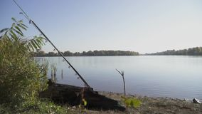 Deux cannes à pêche se trouvant sur la banque de la rivière dans la perspective de l'eau calme, des arbres verts et d'un ciel ble banque de vidéos