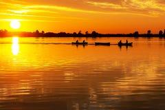 Deux canoës ont tiré en un canot automobile pendant le beau coucher du soleil dans des plas de Zoetermeerse de lac image libre de droits