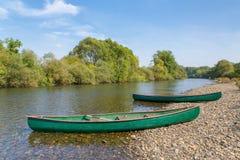 Deux canoës se trouvent sur la banque de la rivière image libre de droits