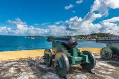 Deux canons de vintage faisant face à l'océan des Caraïbes défendant la baie Photos stock