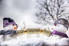Deux caractères de bonhomme de neige tirant un biscuit de Noël Photos libres de droits