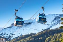 Deux carlingues de funiculaire de Bansko et montagnes de neige Images stock