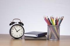 Deux carnets entre l'horloge et les crayons colorés Photo libre de droits