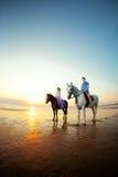 Deux cavaliers à cheval au coucher du soleil sur la plage Hors de tour d'amants Photos stock