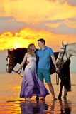 Deux cavaliers à cheval au coucher du soleil sur la plage Hors de tour d'amants Image libre de droits