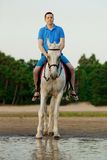 Deux cavaliers à cheval au coucher du soleil sur la plage Hors de tour d'amants Photo stock
