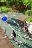 Deux cavaliers de bicyclette suivant les panneaux routiers Images stock