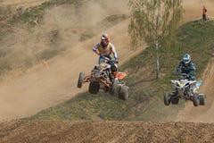 Deux cavaliers de quadruple dans un saut dans la course Photographie stock libre de droits