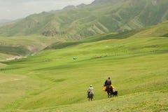 Deux cavaliers entrent à cheval loin dans la vallée entre les montagnes vertes Image libre de droits