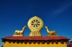 Deux cerfs communs d'or flanquant un Dharma roulent sur Jokhang Photos stock