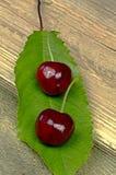 Deux cerises rouges mûres sur une feuille verte Image libre de droits