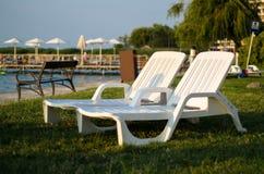 Deux chaises blanches à la plage pendant l'été concept de course Images libres de droits