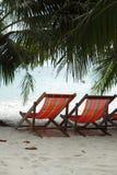 Deux chaises de plage sur la plage sous des palmiers Image libre de droits