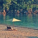Deux chaises et parapluies de plate-forme sur la plage dans la baie rocheuse Image libre de droits