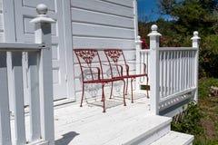 Deux chaises fleuries rouges en métal sur un porche en bois blanc image libre de droits
