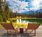 Deux chaises longues en bois sur le rivage du lac Images libres de droits
