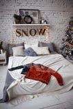 Deux chandails d'hiver étendus sur un lit dans un grenier sur le fond d'un mur de briques image stock