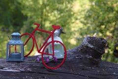 Deux chandeliers et une maquette rouge de bicyclette sur un vieux rondin en bois sur le fond de bokeh de la forêt verte photos stock
