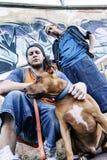 Deux chanteurs de coup sec et dur avec un chien dans un souterrain Photographie stock libre de droits