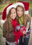 Deux chapeaux de sourire de Santa de femmes retenant un cadeau enveloppé Image stock