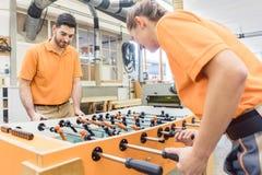 Deux charpentiers jouant le football de table dans la pause photographie stock