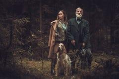 Deux chasseurs avec des chiens et des fusils de chasse dans un habillement traditionnel de tir, posant sur un fond foncé de forêt photo libre de droits