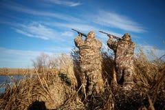Deux chasseurs de canard tirant dans le ciel avec des fusils Image libre de droits
