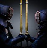 Deux chasseurs de kendo vis-à-vis de l'un l'autre avec le shinai images libres de droits
