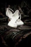 Deux chaussures faciles de mariages blancs de jeune mariée sur un fond foncé Photo libre de droits