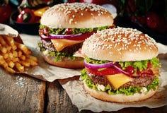 Deux cheeseburgers sur des petits pains de sésame Image stock