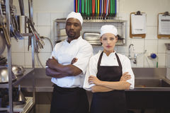 Deux chefs se tenant avec des bras ont croisé dans la cuisine commerciale Images stock