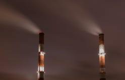 Deux cheminées d'évacuation des fumées contre le ciel Photos libres de droits
