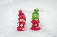 Deux chiffres en bois d'hiver d'un garçon et d'une fille dans la neige Photographie stock libre de droits