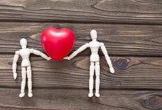 Deux chiffres en bois des personnes tenant un coeur forment sur un fond en bois Images libres de droits