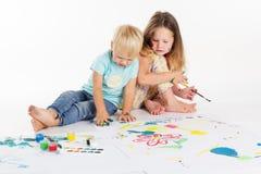 Deux childs dessinent par des peintures d'aquarelle Photos stock