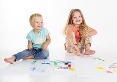 Deux childs dessinent par des peintures d'aquarelle Photo stock