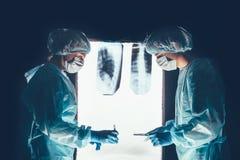 Deux chirurgiens travaillant et se concentrant à la table d'opération photographie stock
