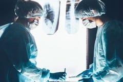 Deux chirurgiens travaillant et se concentrant à la table d'opération image stock
