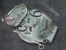 Deux ciseaux ont courbé le mensonge ovale de forme aux bords d'une horloge ronde, à côté d'une autre horloge murale avec un cadra Images libres de droits