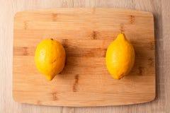 Deux citrons sur la planche à découper en bois photographie stock